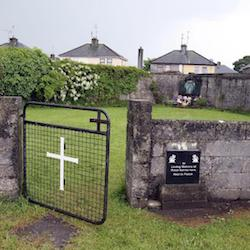 A small walled garden with a stone wall at the front, broken by a metal gate with a large cross mounted on its grille. At the back of the garden is a shrine. Behind the garden's rear stone walls are two pairs of semi-detached houses.