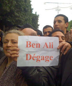 "A group of Tunisians holding a street demonstration. They are holding a sign reading, in red letters on white, ""Ben Ali Dégage [leave]""."