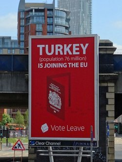 "A red billboard with the claim ""Turkey (population 76 million) is joining the EU. Vote leave"". The poster has an image of a British passport with footsteps leading to it."