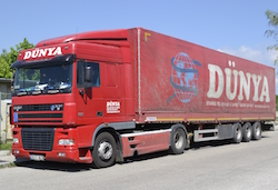"A red DAF XF articulated truck with red tractor and curtain trailer with the name ""Dünya"" and a globe with the land in light blue on it."