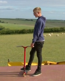 Picture of Tyler, a 14-year-old white boy, riding a scooter on top of a flat-bed farm trailer, against a backdrop of fields with sheep