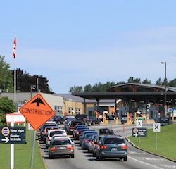 "Two lines of cars approaching a border post with three lanes visible. Signs say ""keep right / garder la droite"", a Canadian flag hangs from a pole to the left and there is an orange, diamond-shaped sign with an up arrow and the word ""Construction"" on it."