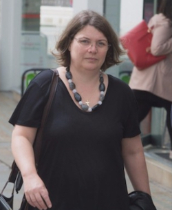 A picture of Valerie Murphy, a middle-aged white woman with thin-rimmed glasses wearing a black V-necked T-shirt and a string of large crystals round her neck, walking along a street past some shops.