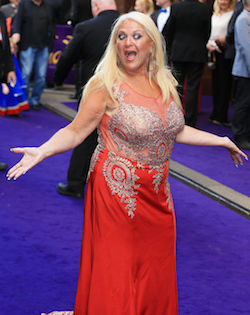 Picture of Vanessa Feltz, a middle-aged white woman with very light blonde hair, wearing a sleeveless red dress with a silver embroidered bodice and a sheer red part at the top, on a purple carpet with her arms outstretched.
