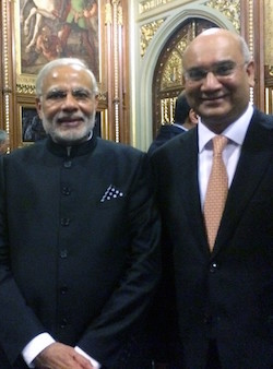 A picture of Narendra Modi, an elderly South Asian man with a white beard wearing a long black jacket, and Keith Vaz, a middle-aged, bald South Asian man with glasses, wearing a white shirt and an orange/brown patterned tie, with a black jacket over the top, in the Palace of Westminster.