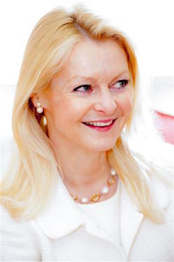 Picture of Vivienne Durham, a late middle-aged, blonde white woman wearing a white jacket with a white top underneath and necklace of large white and orange beads.