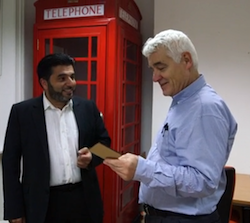 John Ware and an Asian man holding a piece of paper, with an old-style red British phone box behind