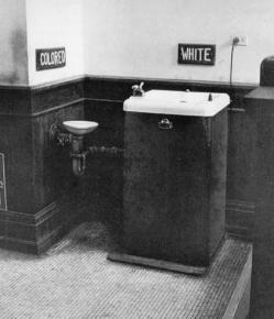 "A black and white photograph showing two water fountains, a tiny one marked ""Colored"" and a large sink with two taps marked ""white"""