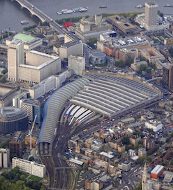 An aerial view of London's Waterloo station, showing lines approaching the station from the bottom of the picture and then the curved platforms, which are under metal and glass canopies, sweeping round towards the top right. Various buildings appear around it including a circular IMAX cinema, the South Bank Centre with a green roof, and the Shell building, a square C-shaped 10-storey art deco building.