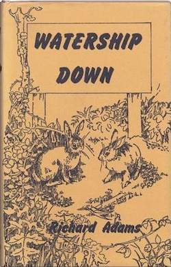 "A yellowish book cover with the words ""Watership Down"" and the author's name ""Richard Adams"" on it, with a drawing of two rabbits among some bushes."