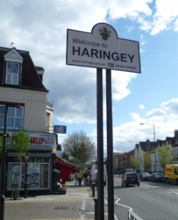 A 'Welcome to Haringey' sign outside a shop on a road in Wood Green
