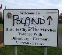 "A sign which originally said ""Welcome to Hereford, historic city of the Marches, twinned with Dillenburg, Germany [and] Vierzon, France"". Hereford has been scrubbed out and replaced with ""Poland""."