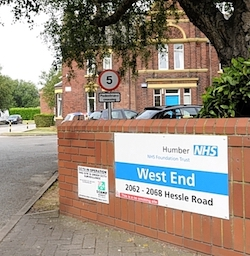 "The entrance to a hospital, with a sign on a red-brick wall saying ""Humber NHS Foundation Trust: West End, 2062-2068 Hessle Road"". A red brick building with a bright blue door stands in the background, while right behind the sign stands a tree whose leaves droop down to partly obscure the building."