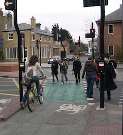Picture of a cycle crossing over a dual carriageway, with a green surface and a symbol of a bicycle on it. A woman is getting ready to ride off on the left, while three pedestrians use it to cross from the other side (instead of the pedestrian crossing which is off to the right).