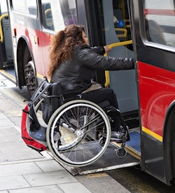 A picture of a woman in a wheelchair using a ramp to board a red London bus