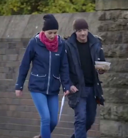 A still of a young white couple walking along the road somewhere in Blackburn. Both are wearing blue clothes, the woman in fairly tight blue jeans with a pink scarf round her neck. The man has two tubs of take-away food in his left hand.