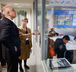 Picture of Michael Wilshaw, a white man wearing a dark suit, accompanied by a middle-aged female teacher in a yellow coat and skirt, watching a lesson through a glass screen.