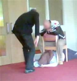 A still from the BBC's Winterbourne View Panorama documentary, showing a male care worker standing over a male patient who is stuck under a chair, while another man sits on the chair.