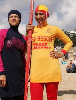"Two women wearing all-over swimsuits. The one on the left has a black suit with pink sleeves and a pink floral motif on the chest. The one on the right is a lifeguard and has a yellow and red uniform suit with ""Surf Rescue"" and the DHL logo on the front. She is holding a red metal pole."