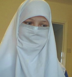 Picture of a white woman wearing a white headscarf and separate face-covering, with an embroidered 'border' under the eyes.