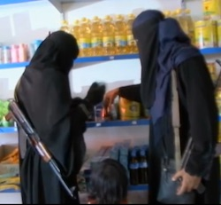 Two women, both in full black robes and veils, standing in a food stop with a small girl in between them. One of the women is holding an assault rifle. The shelves are full of bottles of cooking oil.