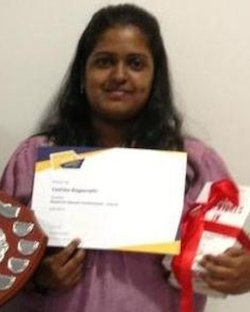 Picture of Yashika Bageerathi, a young South Asian woman, holding a certificate and a stack of books with red ribbons round them