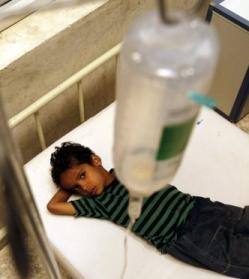 A Yemeni boy lying on a bed with a drip hanging over with, attached to his arm.