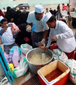 Two men dispensing rice and curry of some sort out of large tubs into small plastic containers. There is a queue of women in black niqaabs waiting.