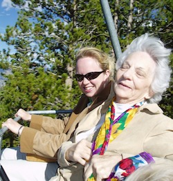 Two white women, one young and one old, on a fairground ride of some sort; the young woman is holding the rail in front of the seat. The old lady, who is wearing a colourful flowery scarf, has her head back and is smiling.
