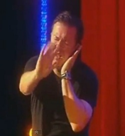 Ricky Gervais on stage in 2007, doing an impression of an ME sufferer