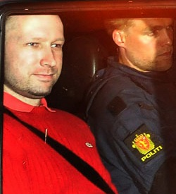 "Anders Breivik in a red coat, being accompanied in a car by a Norwegian policeman with a red and gold badge with the word ""Politi"" underneath"