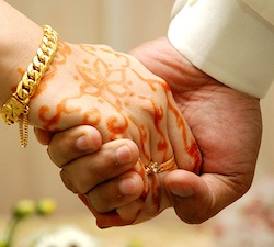 Picture of a man's and a woman's hands, with the woman's decorated in henna