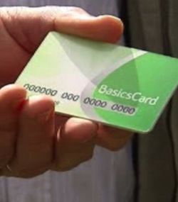 Picture of a hand holding a green credit card-sized card, with the words 'Basics Card' printed on it