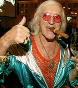 Picture of Jimmy Savile, an old white man wearing pink-tinted glasses, a red string vest and a luminous green tracksuit, with a chunky gold bracelet on his right arm and a glass in his left, and a cigar in his mouth.