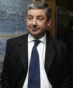 Picture of Paul Goodman, a white man with grey hair wearing a dark-coloured suit, a white shirt and blue tie. To his left is what looks like a school display from an Islamic school, with Arabic writing.