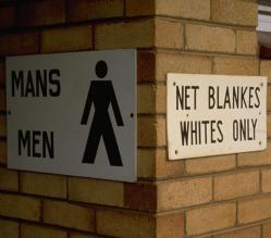"An entrance to a men's public toilet in South Africa under Apartheid. There is a man symbol, with separate signs saying ""Men"" and ""Whites only'"" in English and Afrikaans."