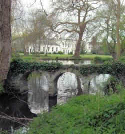 Picture of a park with Morden Hall in the background and an old arch bridge over a river in the foreground