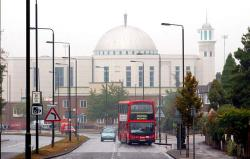 Picture of a dual-carriageway road with a red double-deck bus in the foreground, with road signs and lights seemingly close together, with a red-brick post office depot and a large white domed building in the background.