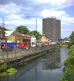 Picture of the River Wandle at Merton. To the left of the river is a main road with a bus garage and several buses visible, with some other houses and shops; in the background is an ugly brown office tower block.