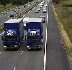 Two trucks travelling side by side in the two leftmost lanes on a British motorway.
