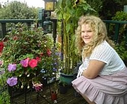Picture of Beth, a young white girl with curly hair wearing a knitted white jumper and a pink skirt, kneeling in front of a rose bush
