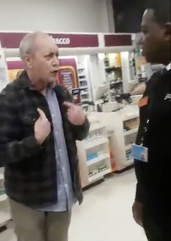 "An old white man points to himself (saying ""I belong here!"") while racially abusing a black security guard in a Sainsbury's shop. The tobacco counter is visible behind him."