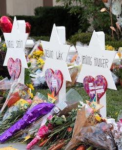 "Three memorials to victims of the Tree of Life synagogue massacre, consisting of names (Daniel Stein, Melvin Wax and Irving Younger) written on white hexagonal stars, with flowers, hearts and stars placed at the feet of the stars, with the word ""hope"" visible on one of them."