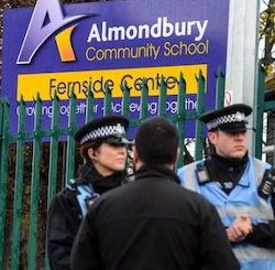 "Two police officers, one male and one female, stand against green railings, behind which is a purple sign with ""Almondbury Community School, Fernside Centre"" in white and yellow writing."