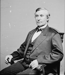 Black and white picture of Jacob M Howard, a middle-aged white man sitting in a wooden chair wearing two dark coloured jackets over a white suit with a bow tie at the neck.