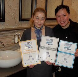 "Three people standing in front of a washbasin in a communal toilet, holding certificates saying ""Loo of the Year 2016"""