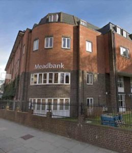 A picture of Meadbank care home, a red-brick building on a corner with the name 'Meadbank' in large white letters on the rounded corner, with a brick wall topped by a black metal railing in front of it.