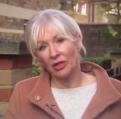 Nadine Dorries, a middle-aged white woman white grey and white hair wearing a light grey top under a light brown coloured jacket.
