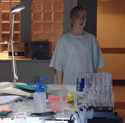 Still from Holby City of Jac Naylor, a middle-aged white woman wearing no make-up and with blonde hair tied behind her head, wearing a hospital gown, standing in a darkened laboratory in front of a table with a desk lamp shining down and some test tubes in a rack.