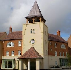 The Whistling Witch, a tower on a corner in Poundbury with a brick portico at street level and a four-sided spire at the top.